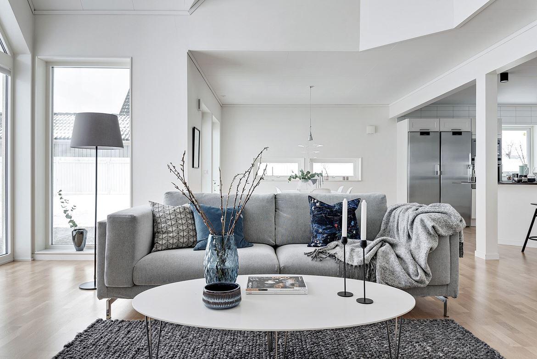 Foto på grå soffa och vitt soffbord med blå vas