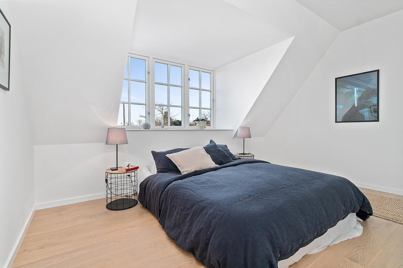 foto på dubbelsäng i ett ljust sovrum