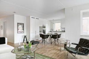 foto på kök med trägolv och stolar samt en stor grön matta