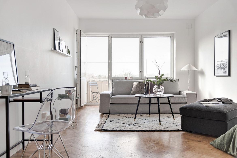 vardagsrum med matta och grå soffa