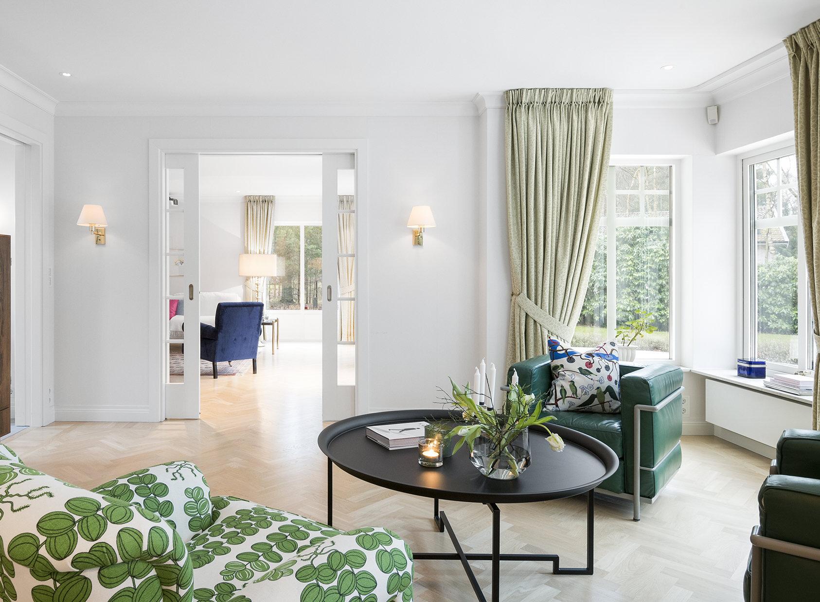 grön fåtölj med stort brickbord och gröna gardiner
