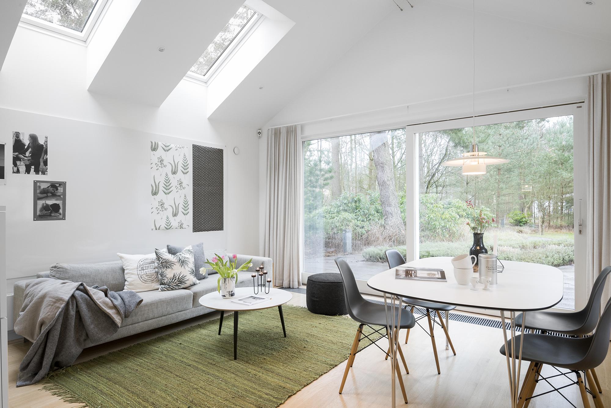 foto på vardagsum med stor ljus soffa och ett matbord med stolar