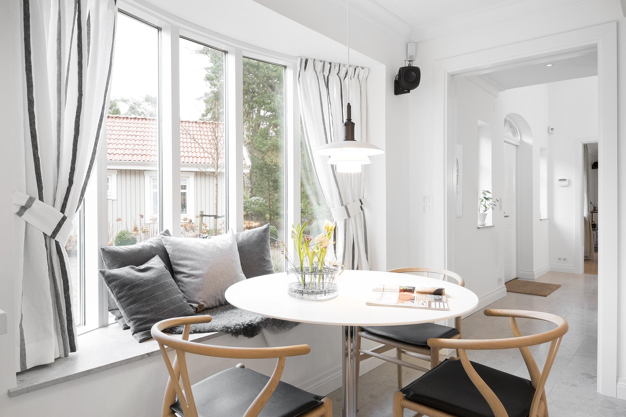 foto på stolar och bord i ett ljust kök samt bänk med kuddar