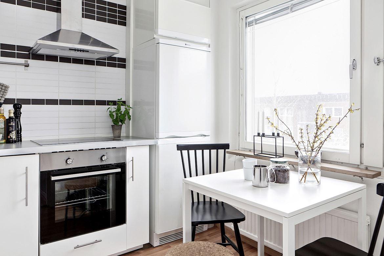kök med vitt bord och svart stol