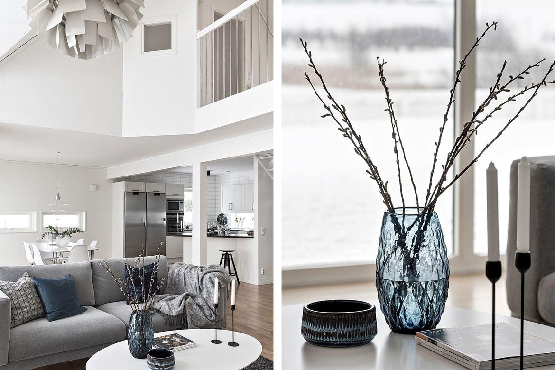 blå vas på bord och en grå soffa med ljus
