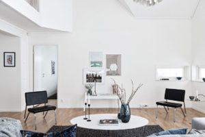 foto på vitt soffbord med vas och vitt vägg med konst