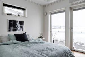 foto på dubbelsäng med blått överkast och tavla ovanför sängen