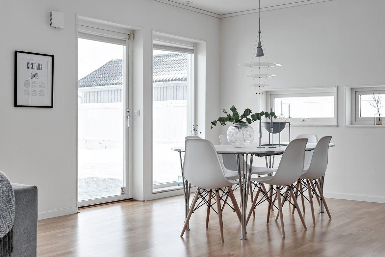 foto på ljust rum med stort matbord med vita moderna stolar