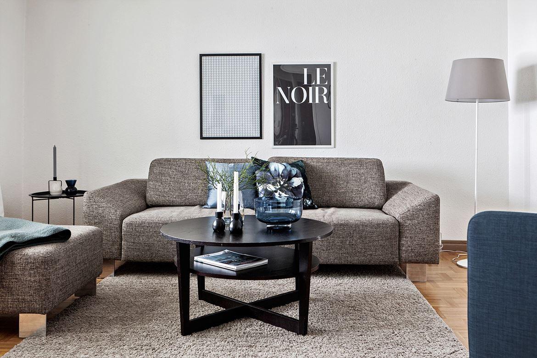 grå soffa med svart soffbord framför