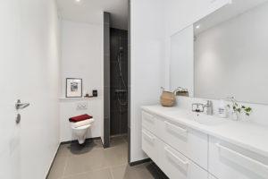 foto på badrum med vitt kakel och stor spegel