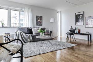 Ljust vardagsrum med en grå soffa