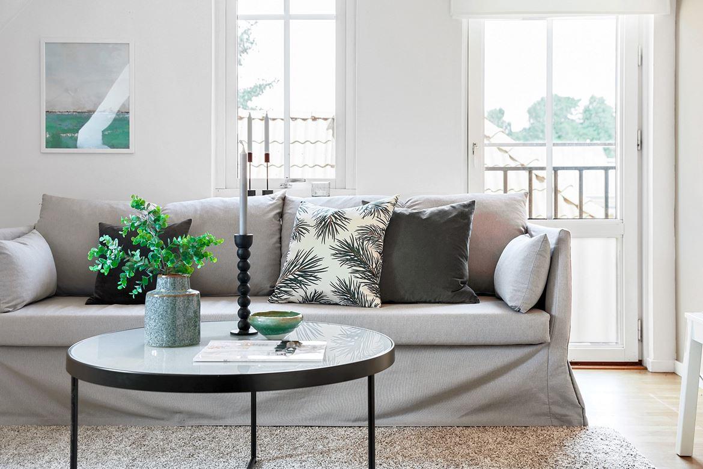 inredning vardagsrum grå soffa kuddar blomma