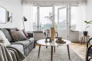 inredning grå soffa vita gardiner parkettgolv